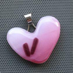 Ljusrosa hänge i hjärtform med 2 små lila streck. Silverfärgat bakstycke i form av hjärta